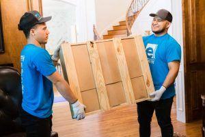 two men with element moving & storage, llc blue t shirts moving a crate
