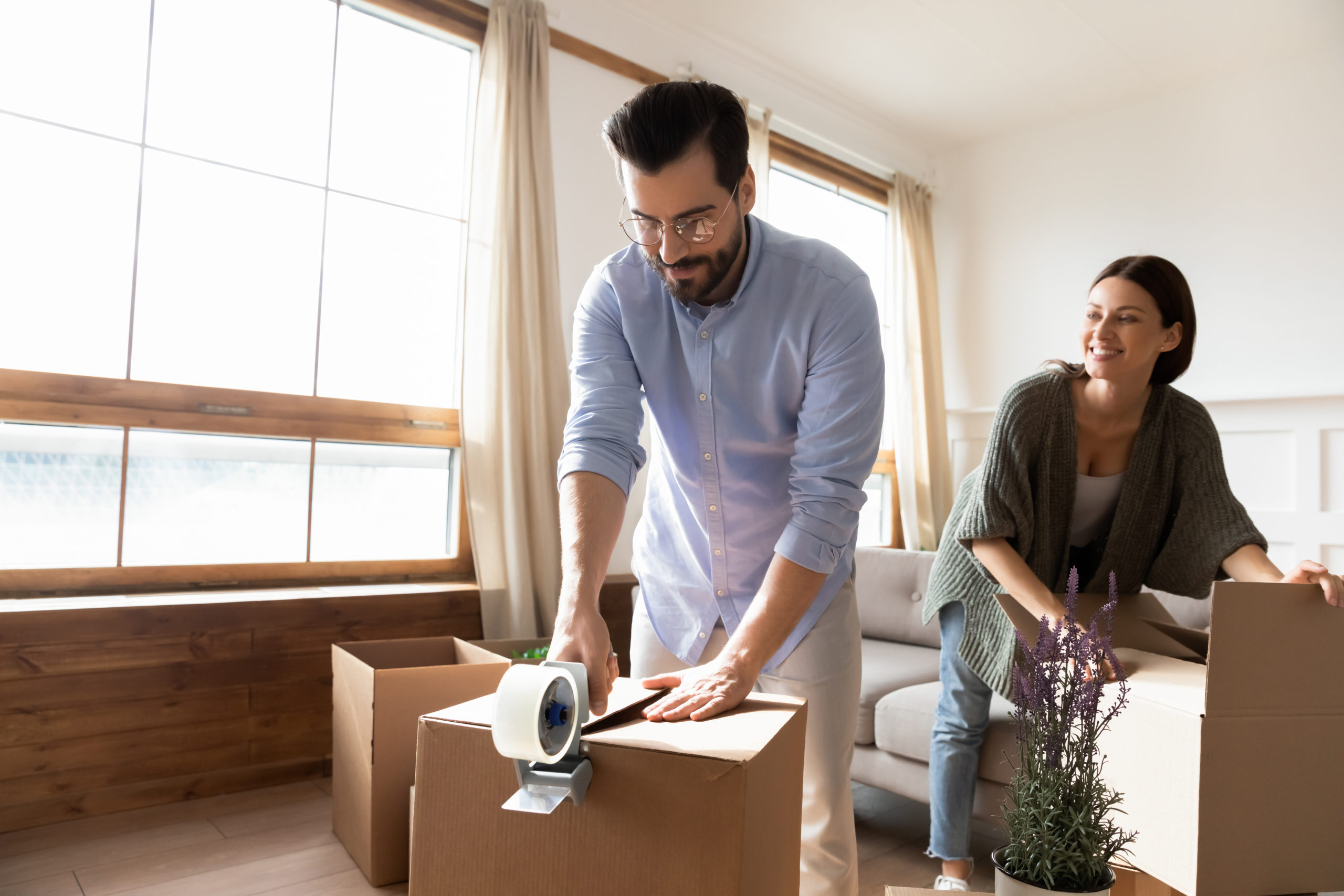 Happy young family packing boxes with tape dispenser