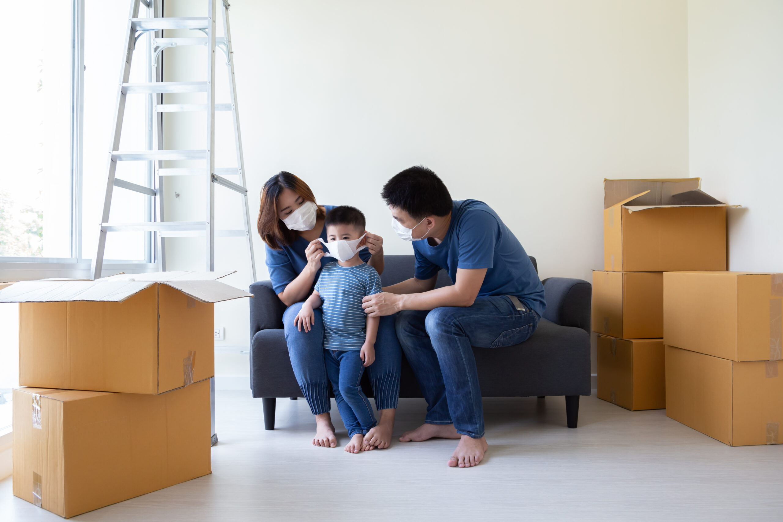 Asian family wearing protective medical mask for prevent virus covid-19 during moving day and relocating at new home.