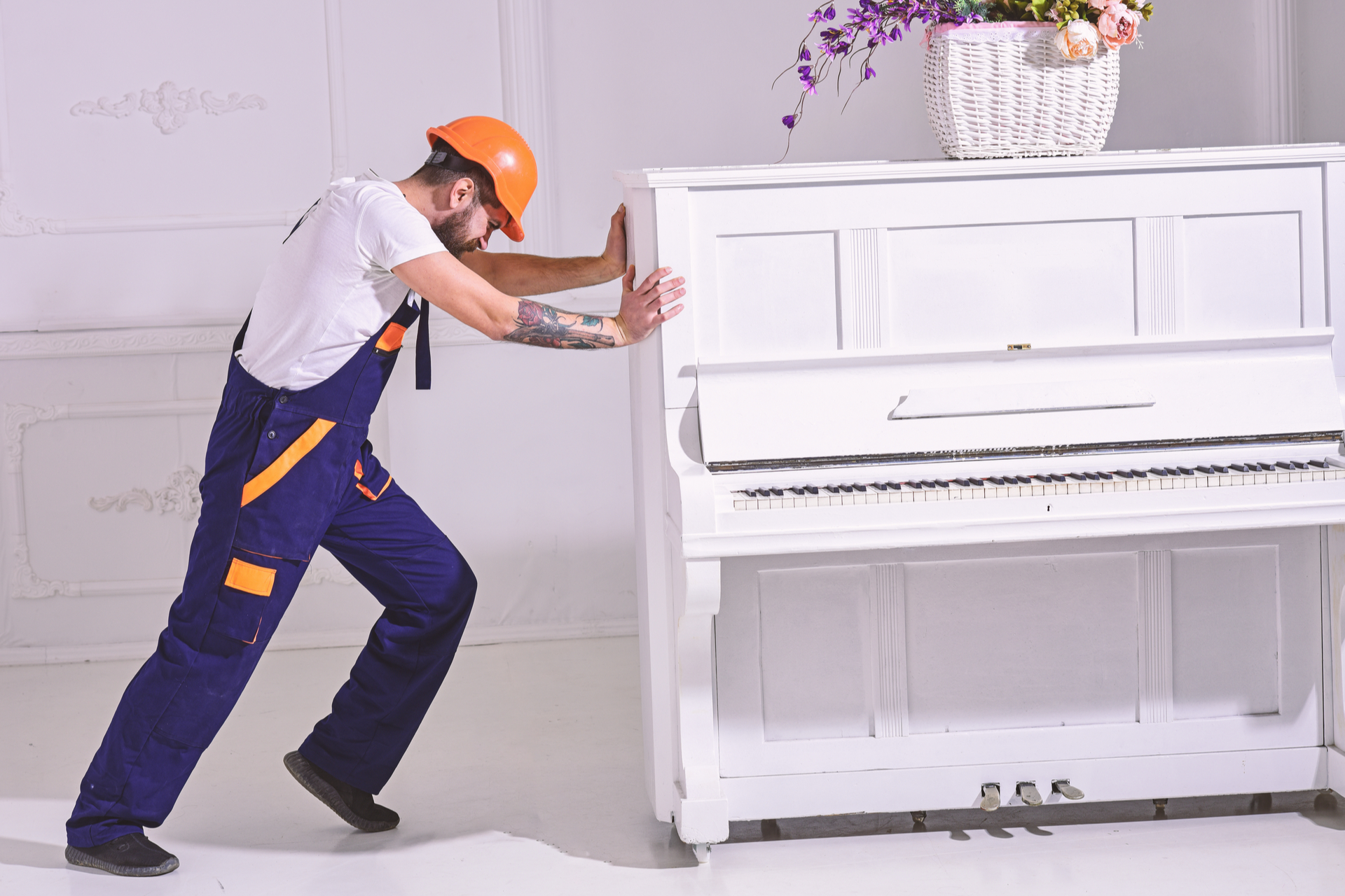 Man with beard worker in helmet and overalls pushes, put efforts to move piano