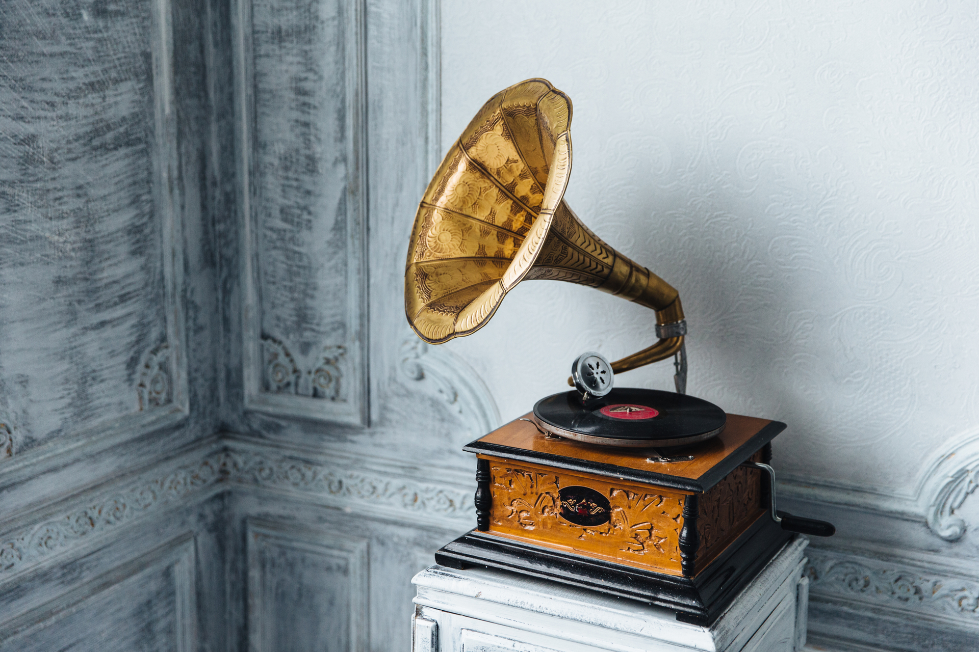 Old gramophone with plate or vinyl disk on wooden box.